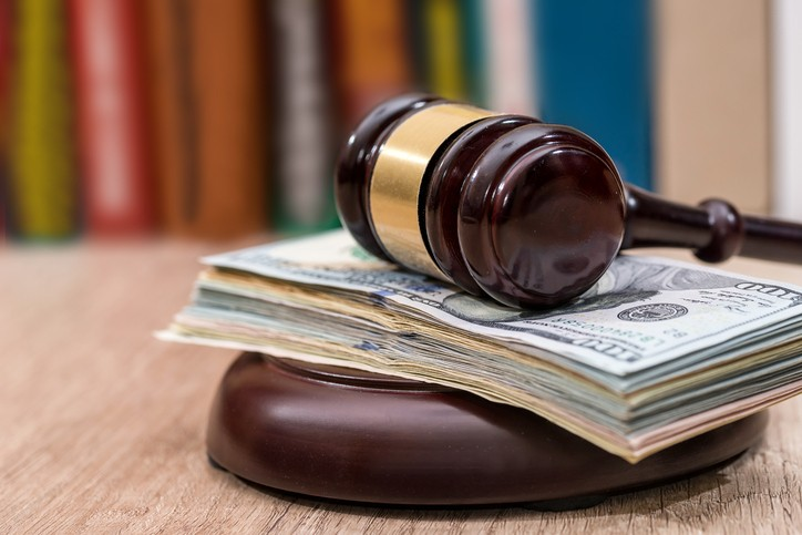 Judge gavel with dollars, books on  wooden desk close up.